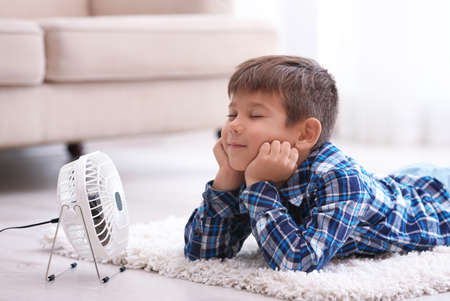 Little boy refreshing from heat in front of small fan at home