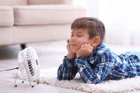 Mały chłopiec orzeźwiający się z upału przed małym wentylatorem w domu Zdjęcie Seryjne