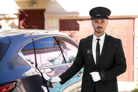 Junger hübscher Fahrer, der nahe Luxusauto steht. Chauffeurservice Standard-Bild