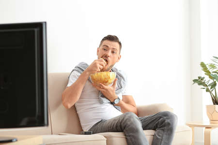 Man with bowl of potato chips watching TV on sofa in living room Stock fotó