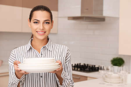 Beautiful young woman holding stack of clean dishes in kitchen