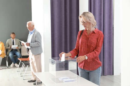 Woman putting her vote into ballot box on table indoors