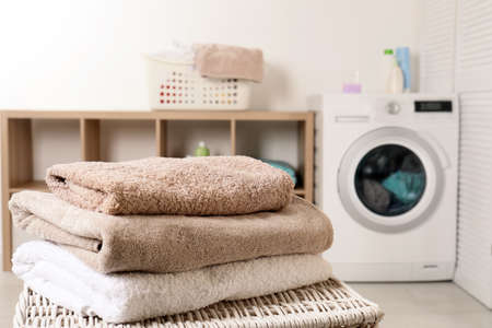 Stack of clean soft towels on basket in laundry room. Space for text Stock Photo