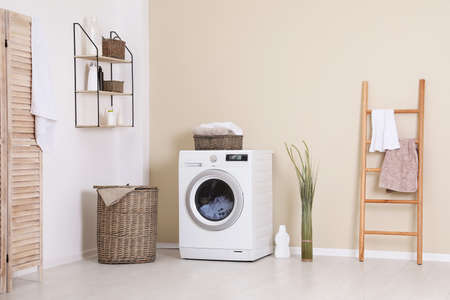Laundry room interior with washing machine near wall 写真素材 - 112071416