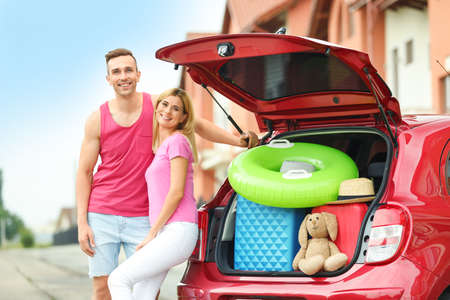 Happy couple near car trunk with suitcases outdoors Archivio Fotografico