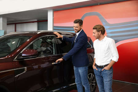 Salesman with customer in modern car dealership Stockfoto