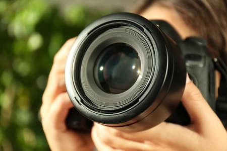 Fotógrafo de sexo femenino con cámara profesional sobre fondo borroso, primer plano