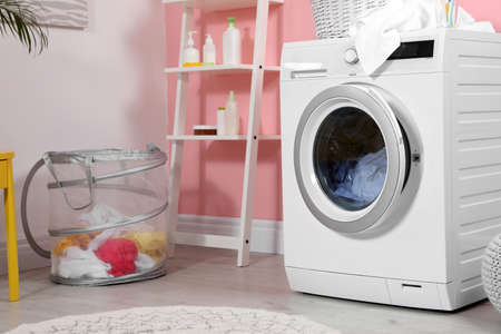 Modern washing machine near wall in laundry room