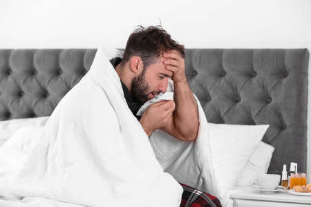 Ill man suffering from cough at home