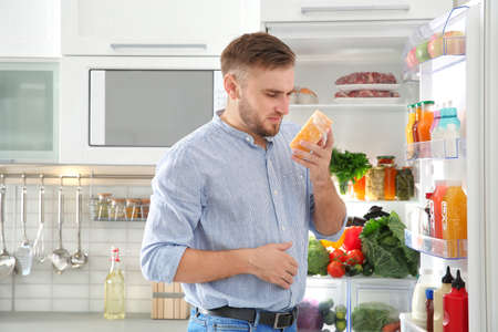 Man feeling bad smell from stale cheese near refrigerator at home Stock Photo