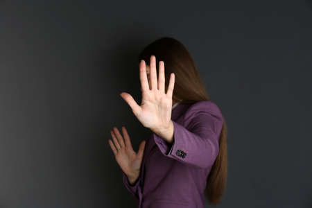Woman showing stop gesture on dark background. Problem of sexual harassment at work