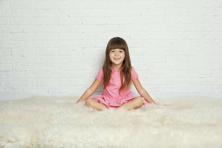 Cute little girl sitting on fur rug against brick wall