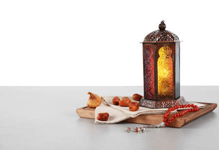 Muslimische Lampe, Termine und Gebetskette auf dem Tisch vor weißem Hintergrund. Platz für Text
