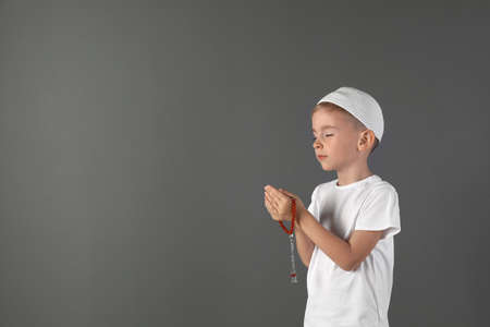 Little Muslim boy praying on gray background. Space for text
