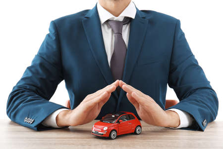 Insurance agent covering toy car on table against white background