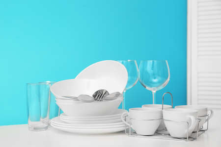 Set of clean dishware on table against color background