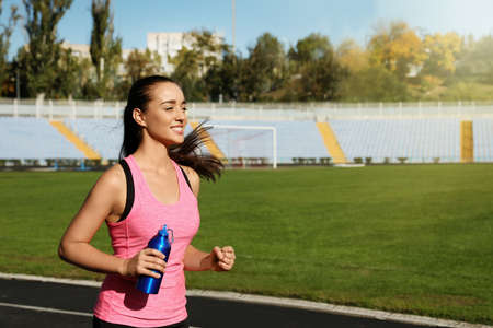 Sporty woman running with bottle of water at stadium on sunny day. Space for text 스톡 콘텐츠