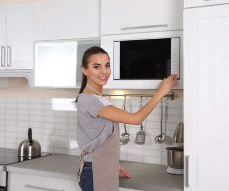 Young woman using microwave oven at home 版權商用圖片