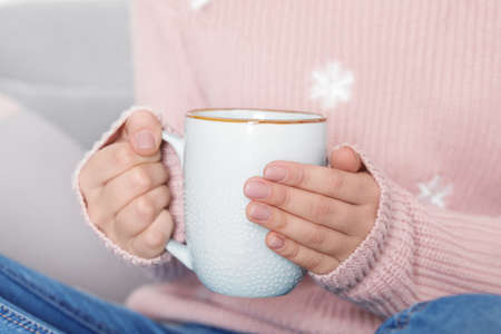Young woman in warm sweater holding cup of hot drink, closeup