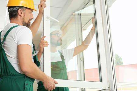 Construction workers installing new window in house Standard-Bild - 112586663