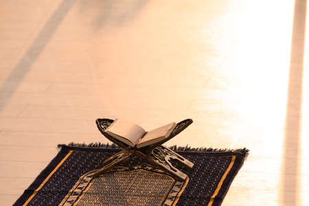 Rehal with open Quran on Muslim prayer mat indoors. Space for text