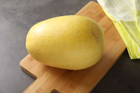 Whole ripe spaghetti squash on gray table