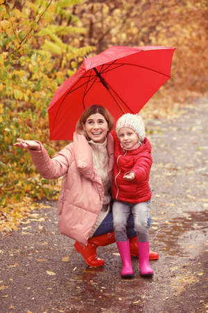 Mother and daughter with umbrella in autumn park on rainy day