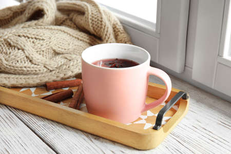 Composition with cup of hot winter drink on sill near window. Cozy season