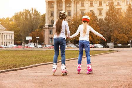 Cute children roller skating on city street