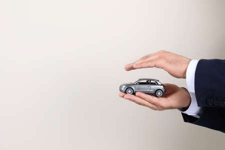 Male insurance agent holding toy car on light background, closeup. Space for text