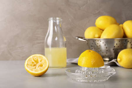 Composition with glass squeezer and lemons on table