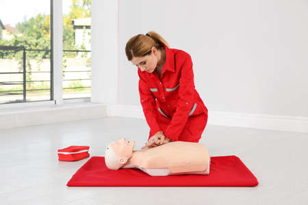 Woman in uniform practicing first aid on mannequin indoors Banque d'images