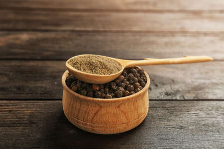 Spoon with powdered black pepper and corns in bowl on wooden table 免版税图像