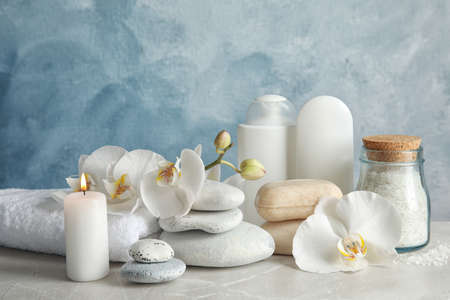 Beautiful composition with candle and spa stones on light table