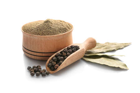Bay leaves, scoop with black pepper grains and bowl of powder on white background 免版税图像