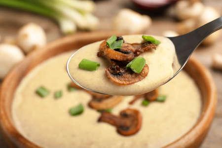 Spoon with fresh homemade mushroom soup over bowl, closeup