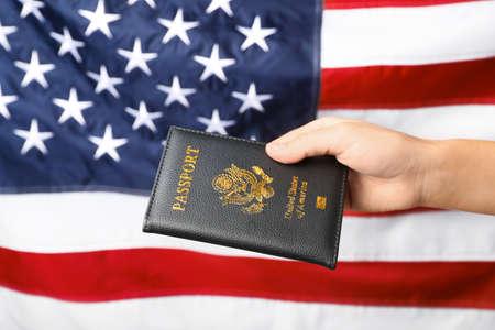 Woman holding passport against flag of USA, closeup