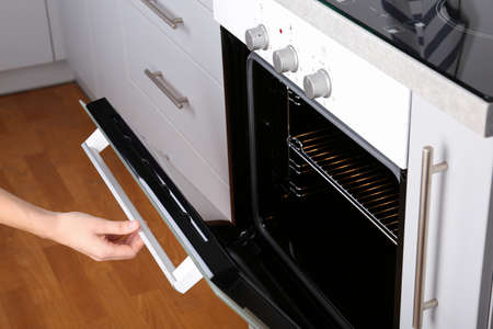 Woman opening electric oven in kitchen, closeup