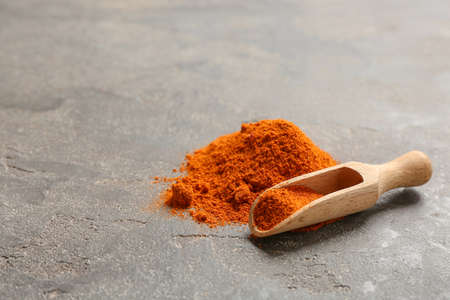 Scoop and powdered red pepper on table, space for text. Aromatic spice Reklamní fotografie