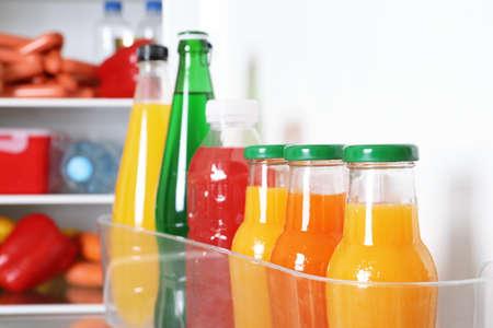 Bottles of beverages on refrigerator door shelf, closeup