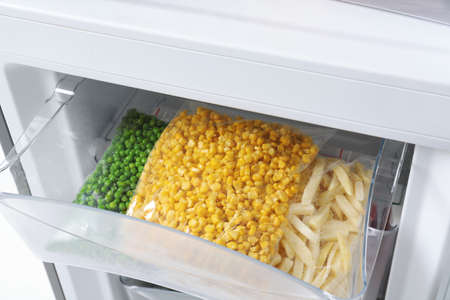 Plastic bags with frozen vegetables in refrigerator, closeup Banque d'images - 112074999