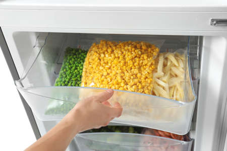 Woman opening refrigerator drawer with frozen vegetables, closeup