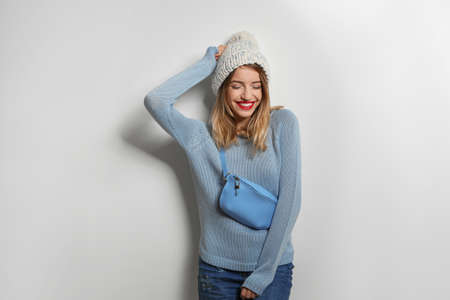 Beautiful young woman in warm sweater with bag on white background Standard-Bild
