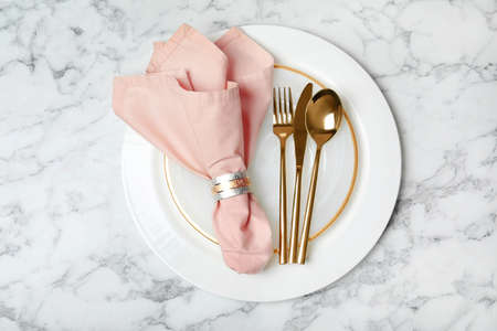 Plate with golden cutlery and napkin on marble background, top view. Festive dinner setting