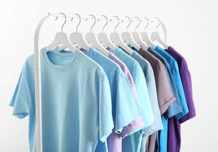 Vêtements pour hommes accroché sur un rack de garde-robe sur fond blanc
