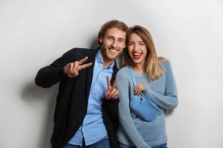 Young woman in warm sweater and man wearing knitted cardigan on white background