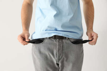 Man showing empty pockets on light background Banco de Imagens