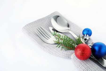 Cutlery, napkin and Christmas decor on white background, closeup. Festive table setting