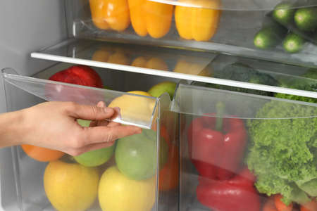 Woman opening refrigerator drawer with fresh fruits, closeup Imagens