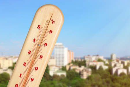 High temperature on thermometer and cityscape view